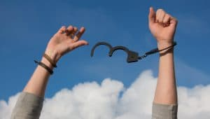 hands raised to the sky breaking free of handcuffs | Bankruptcy