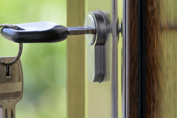 Key hanging in a polished wooden door | Buying a House