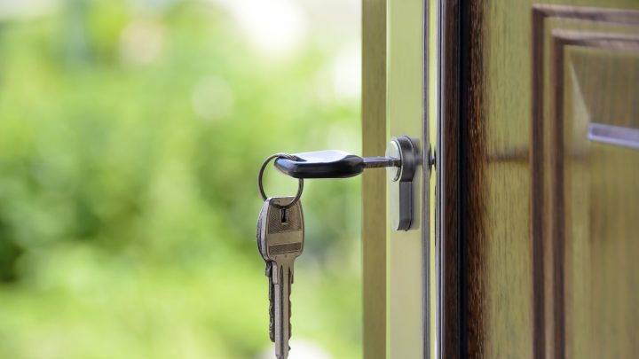 Key hanging on a polished wooden door | new Canadian Mortgage rules