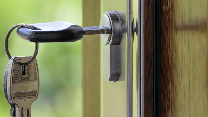 Key hanging in a polished wooden door   Buying a House