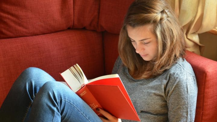 Student Loans | Young woman reading a book on a couch