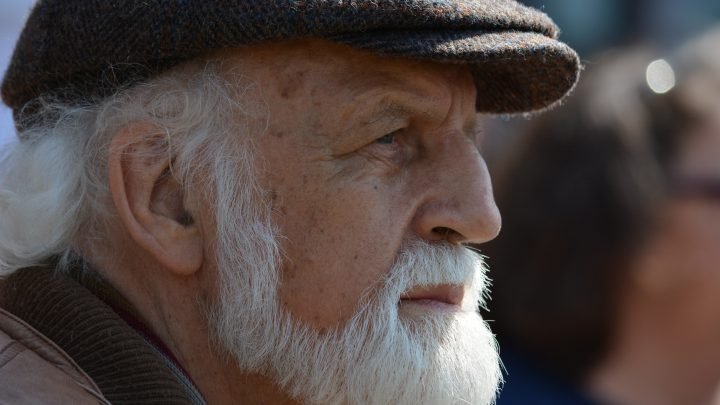 Retirement | Older man with a white beard and dark cap looking out into the distance