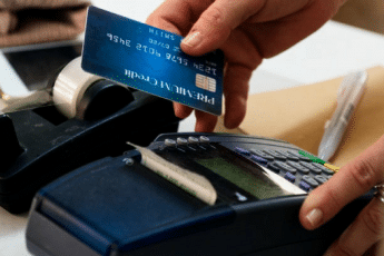 Loyalty Cards | Man sliding credit card through POS machine
